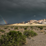 Emigrant Peak along highways 95 and 6 under storm clouds with a rainbow in background.